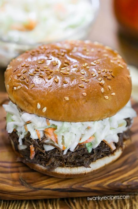 Instant Pot Pulled Pork with a tangy and sweet North Carolina vinegar sauce on a sandwich with coleslaw.